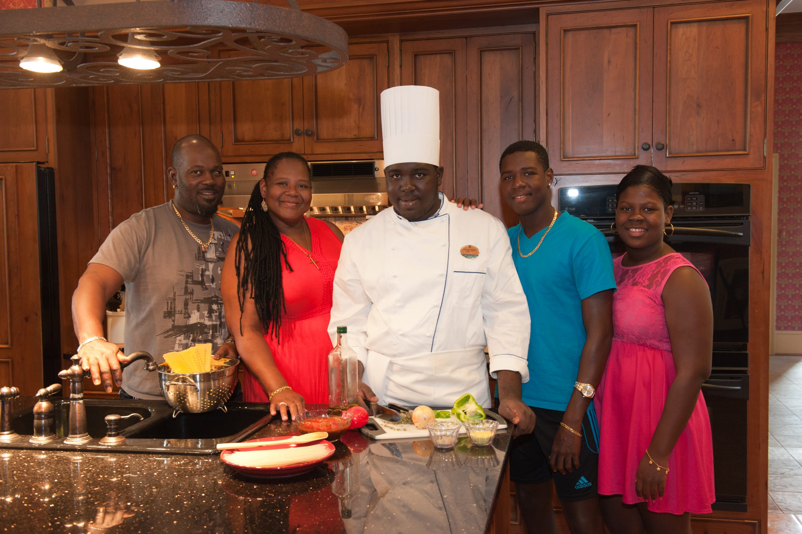 Josh Sobers-Henry, in white chef hat and clothes preparing food, and Family in The Woodmont House kitchen