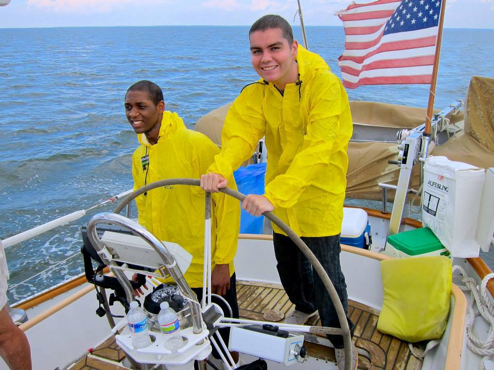 Two boys steering sail boat on the Chesapeake Bay