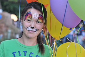 Image of a resident with festive face paint and balloons