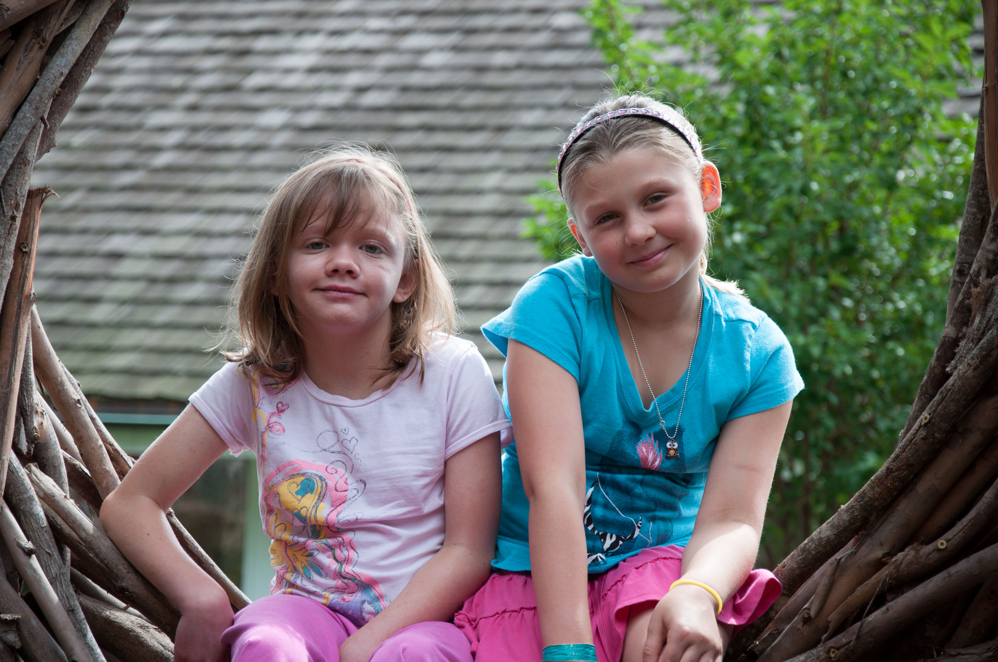 two sisters smiling and sitting on the nest, a structure built out of sticks, on The Children's Inn's playground