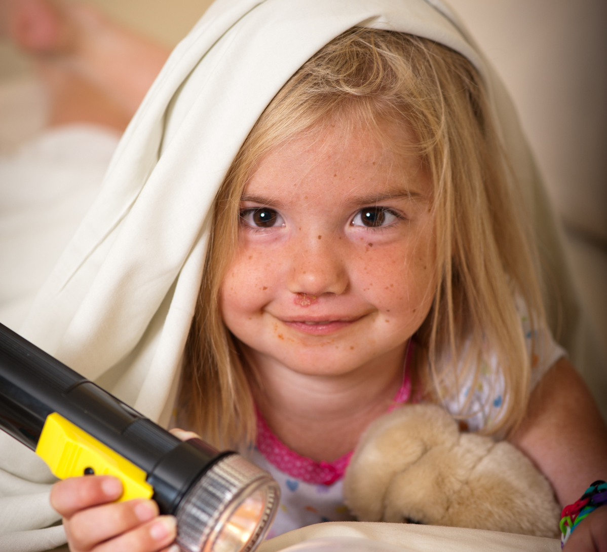 Makenna, little girl, with flashlight under blanket holding a teddy bear