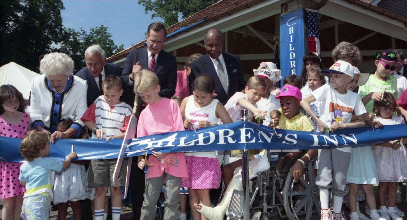 President George H.W. Bush and Barabara Bush with kids cutting the ribbon at Children's Inn opening