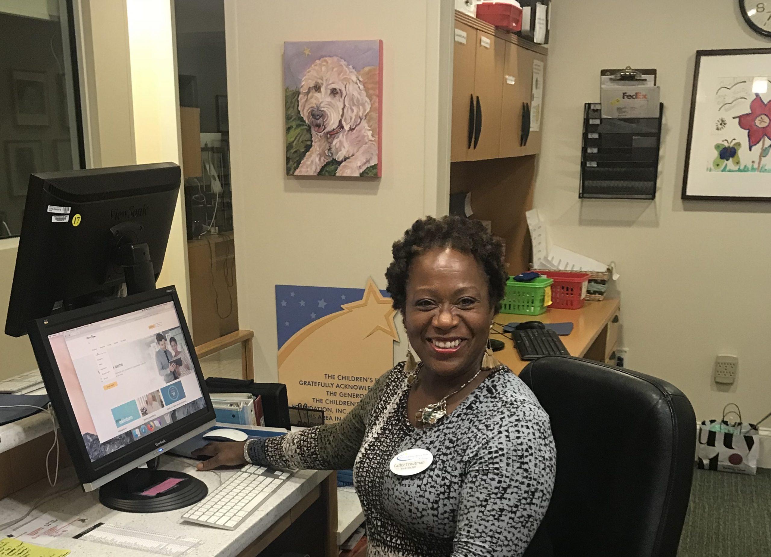 Cathy Troutman at volunteer desk of The Children