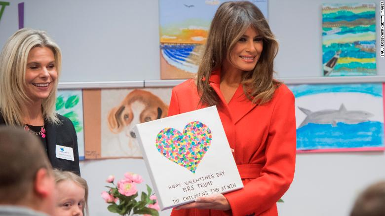 First lady Melania Trump holds up a gift as she visits with children who are currently patients at the National Institutes of Health (NIH) at The Children's Inn