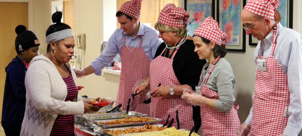 Booz Allen volunteers serve dinner to residents