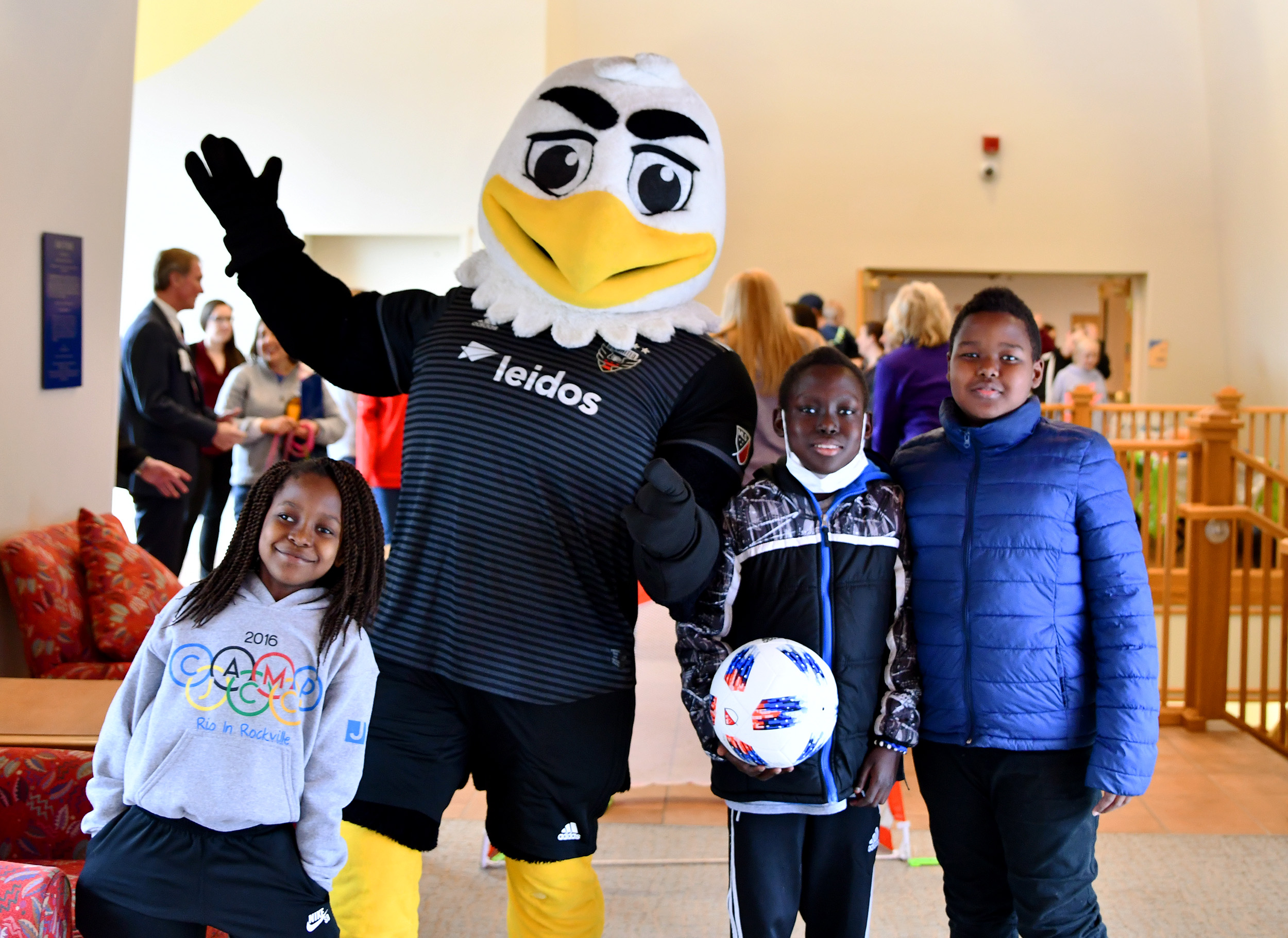 Eagle mascot with three kids pose for a photo