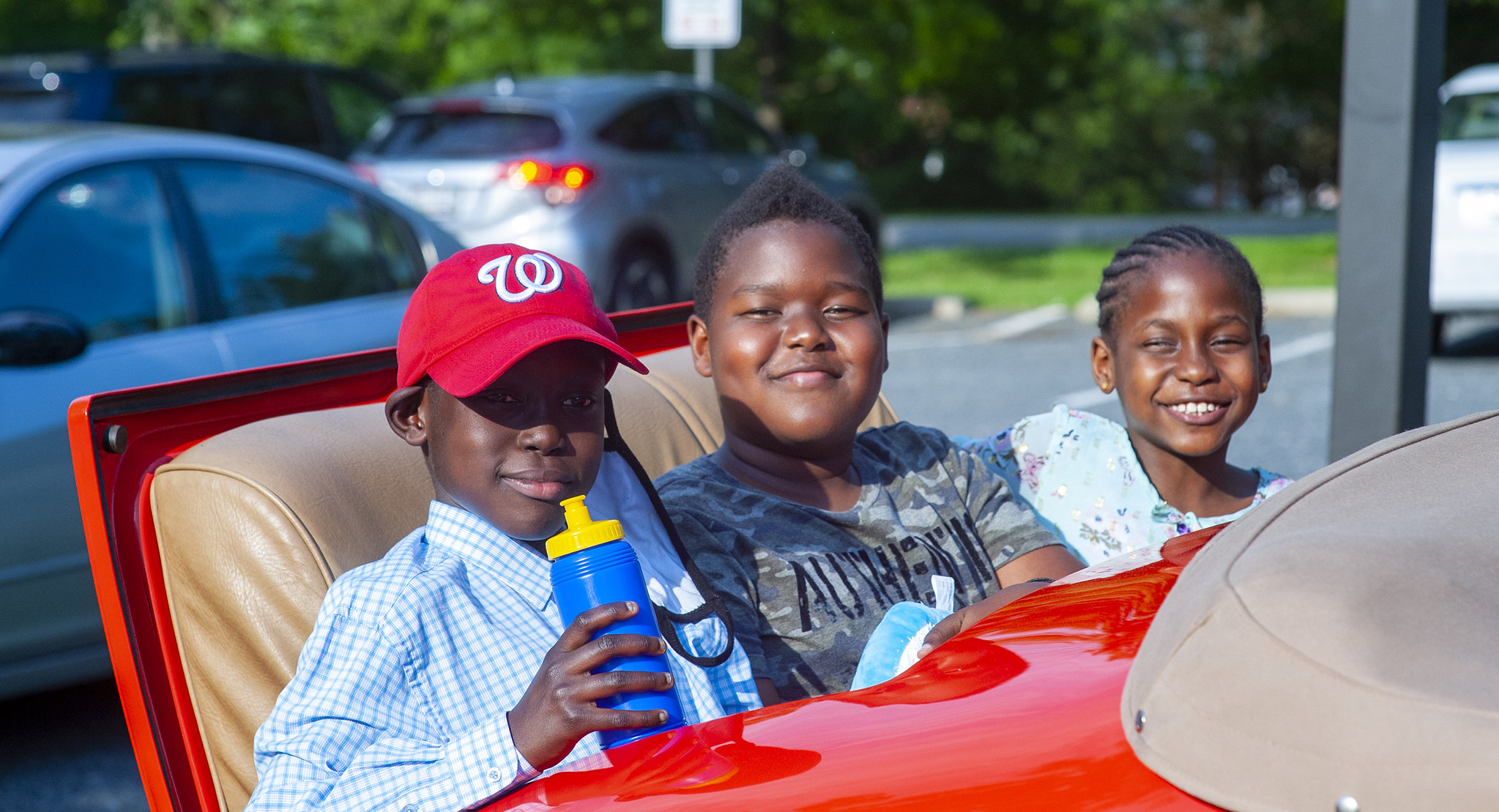 Three kids have fun outside at the car show