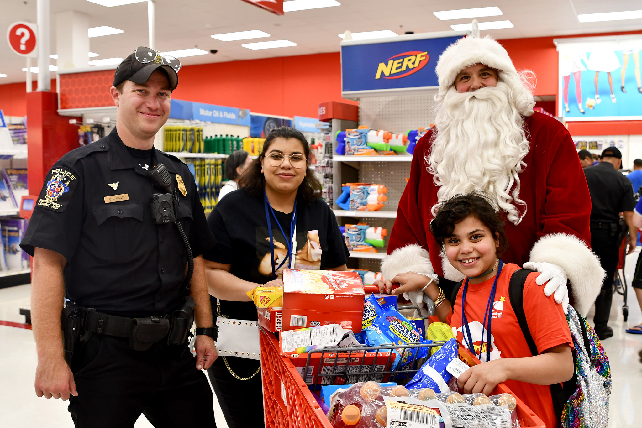 Inn residents with a cart full of goodies pose with a Montgomery County Police officer and Santa Claus
