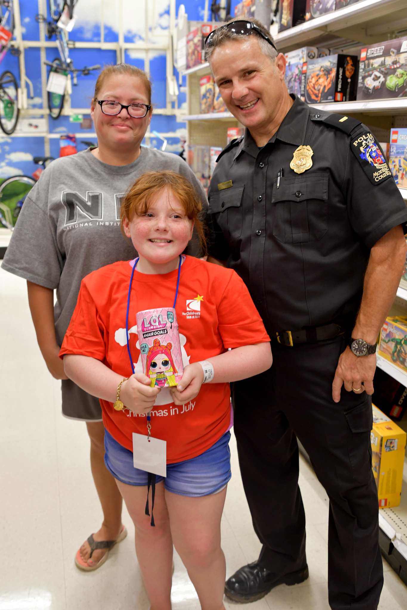 Inn residents Avery and Julie pose with Montgomery County Police Officer David McBain, who helps organize the yearly Christmas in July event