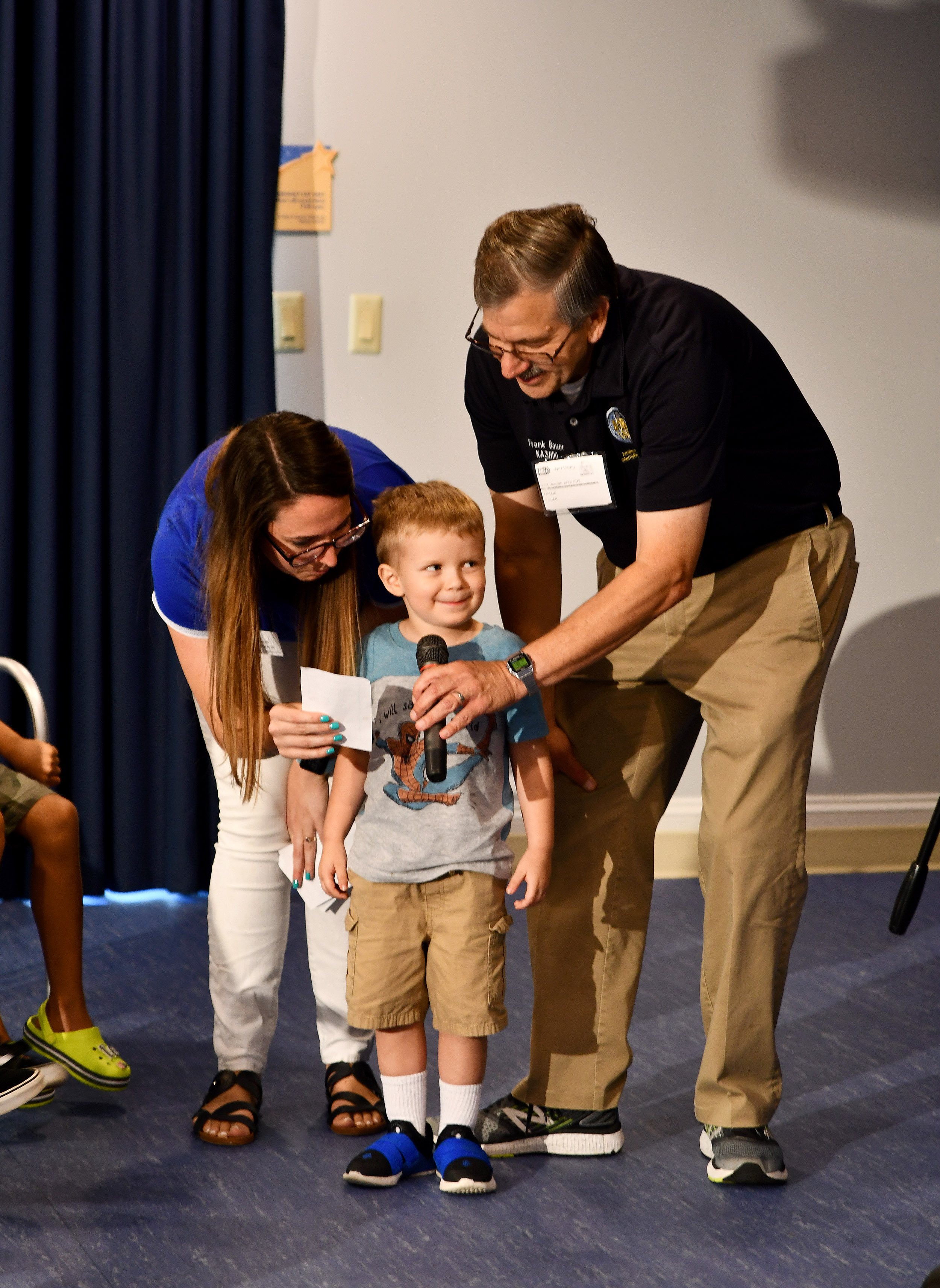 Inn resident Carson asks astronaut Clay Anderson a question, with the help of Inn staffer Tori and ARISS rep Frank