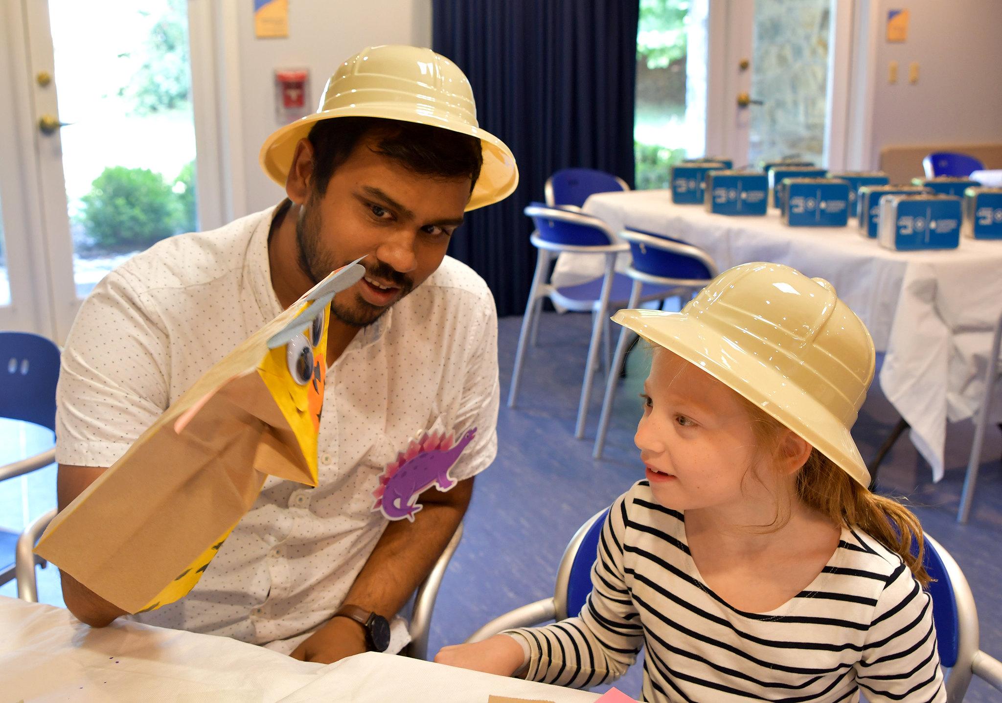 Inn staff member Javin helps Katherine make a hand puppet