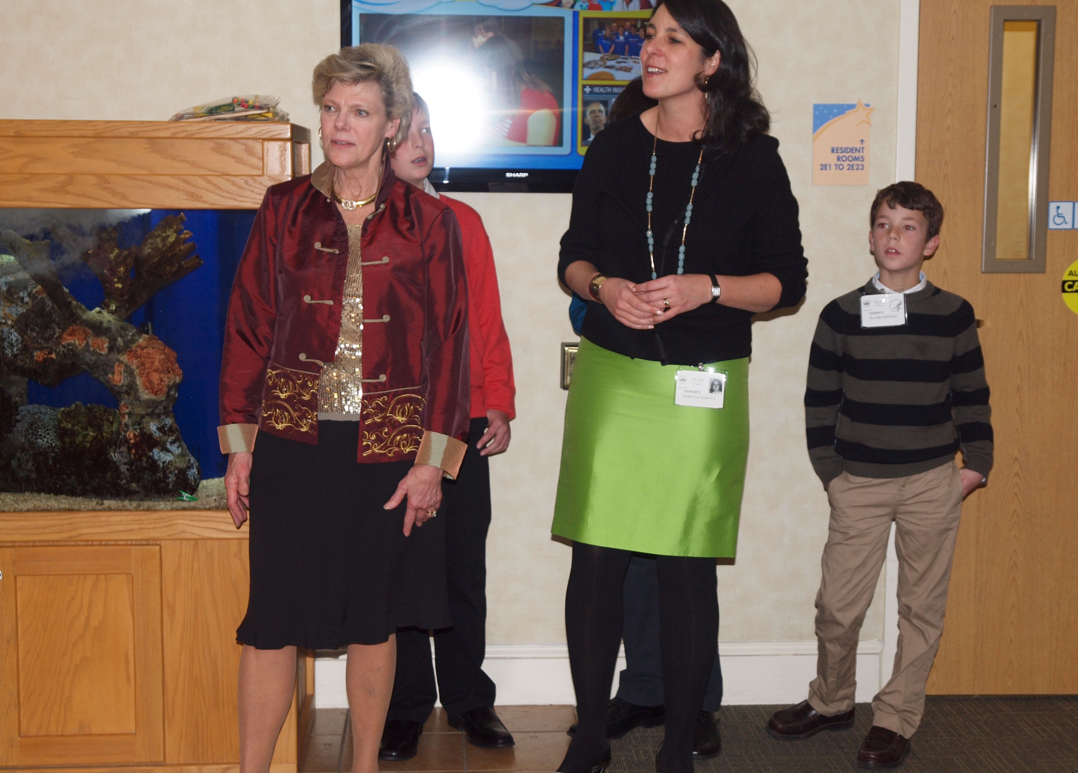 Inn board member Cokie Roberts carols for residents with her family