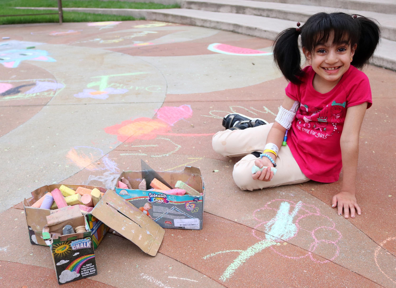 Muna plays with chalk on the playground