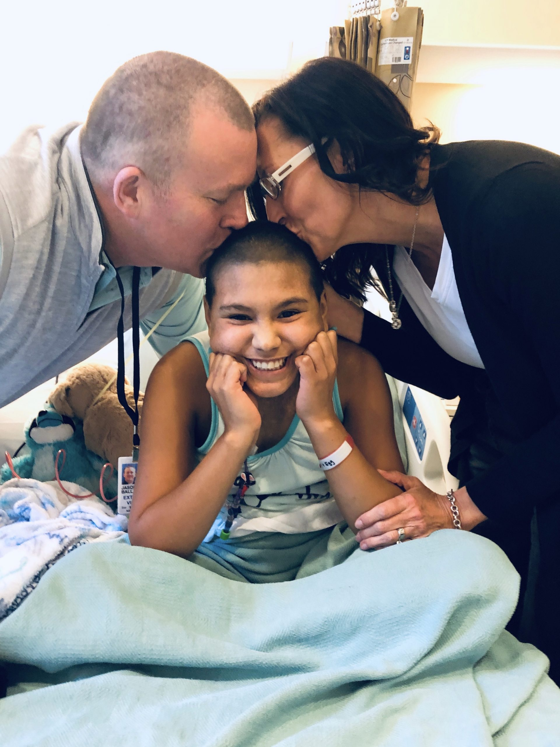 Emi in the hospital with her parents
