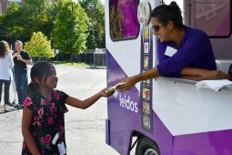 Girl buying ice cream from Leidos ice cream truck