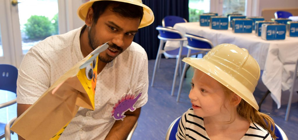 Man entertaining a child with hand puppet